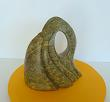 Sculpture abstraite en stéatite de couleur verte, veinée de jaune, nommée le charme du neuf.
