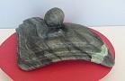 Sculpture abstraite en stéatite, de couleur vert foncé, nommée` lever de soleil sur la rizière`.